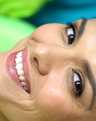 Woman in dental chair smiling with porcelain veneers in Boston