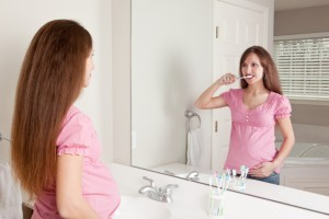 pregnant woman brushing her teeth to avoid periodontal diseasepregnant woman brushing her teeth to avoid periodontal disease