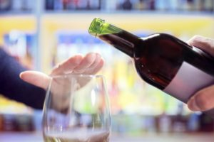 Woman's hand covering glass to reject more wine